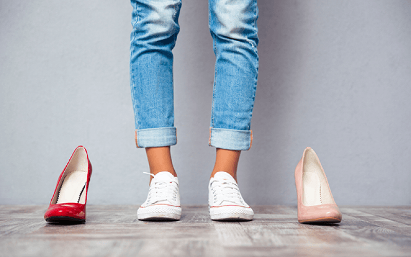 vrouw op hakken of platte schoenen sneakers